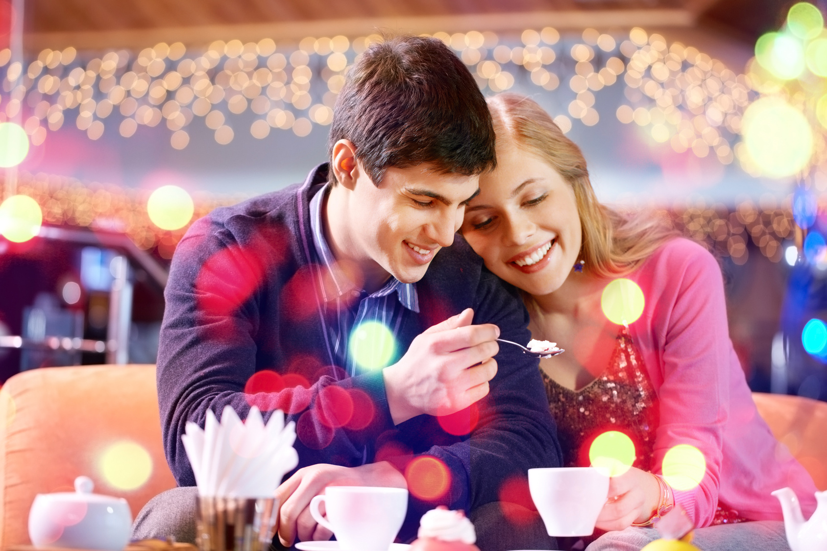 Cute couple eating cake and drinking tea in restaurant