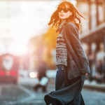 Trendy fashion woman in coat walking on the street, city scene