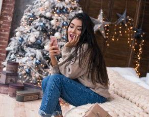 Beautiful lifestyle girl with smartphone typing a message and using internet. Congratulations to friends. Happy message from best friend. Real emotions with lovely friends. Christmas and New Year 2018