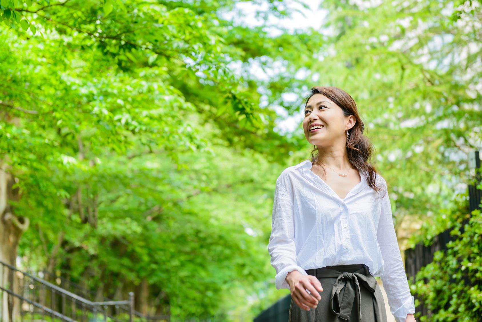 新緑の中を歩く女性