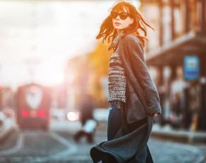Trendy fashion woman in coat walking on the street, city scene