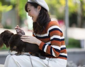 ペットと公園を散歩する女性